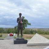 Скульптура девочки по имени Мила с цветком в руке.